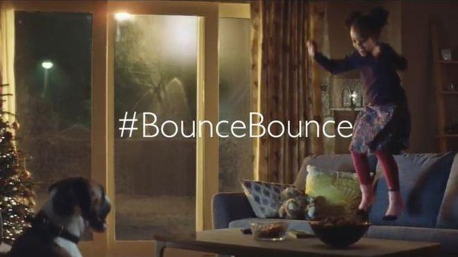 boxer dog watching girl bouncing on sofa with text saying #BounceBounce